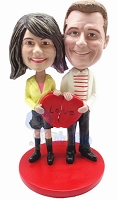 A couple standing together on a base, each holding part of a heart to makes them complete custom bobble head doll